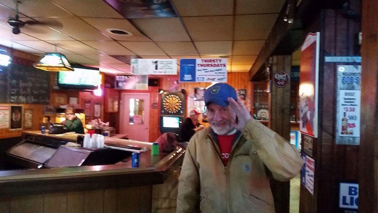 Michael Jacobs, 63, waves as he enjoys an afternoon full of football and politics at Bob's Bar. Photo by Brandon Anderegg.